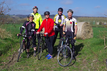 A group of 5 cyclists out on a day ride on a sunny day standing on the edge of a field.