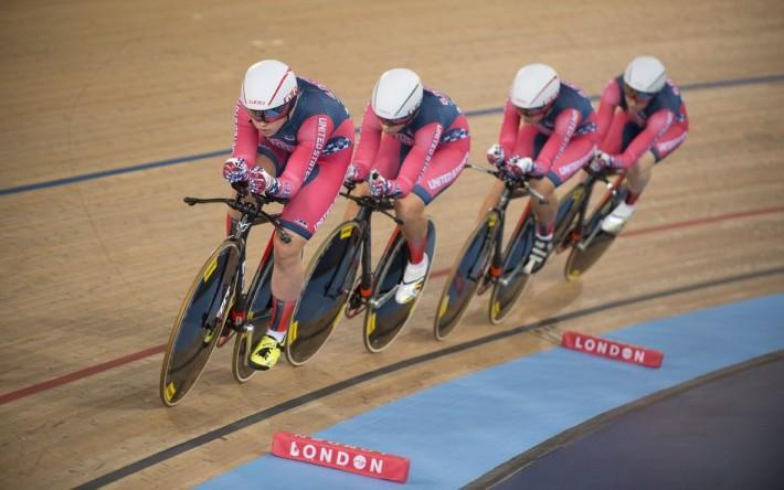 Four women track cyclists racing around the track in pink and grey kit