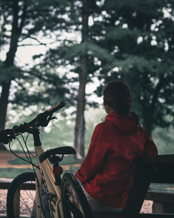 Woman sitting on bench under trees next to her cycle