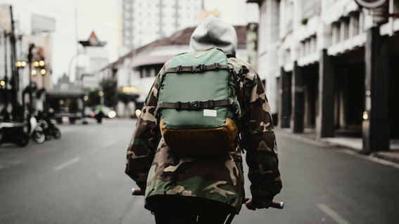 Man seen from behind with green rucksack cycling along city street