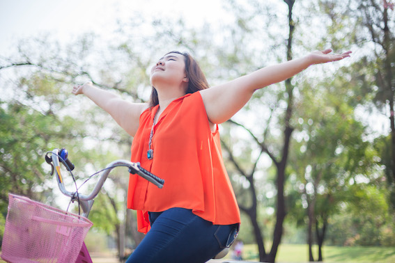 Asian woman in red top with outstretched with bicycle outdoor in a park